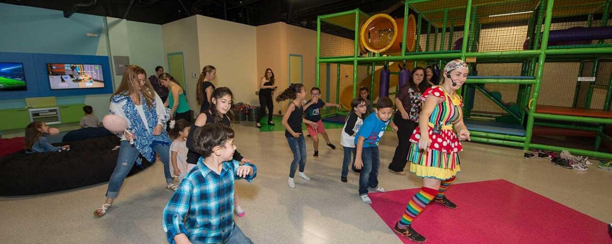 Kids dancing along to a game with a BirthdayLand staff member.