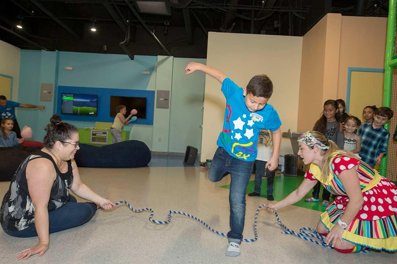 A child jumps over a rope as part of a birthday party game.