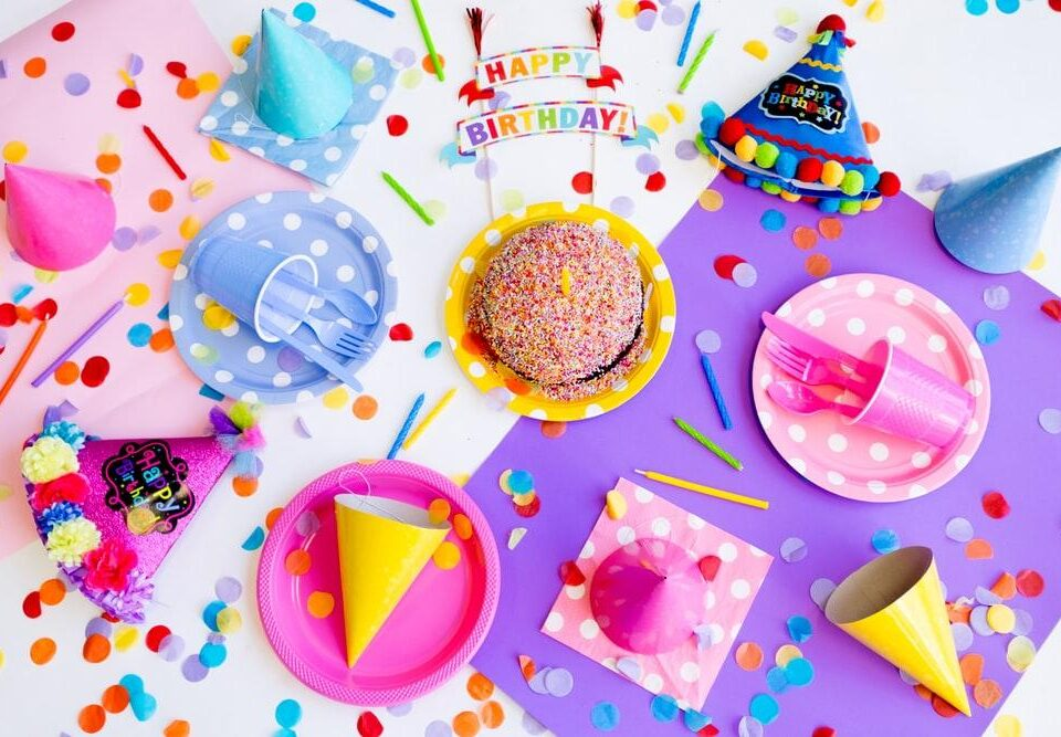 a birthday station with cake, plates, party hats, and confetti